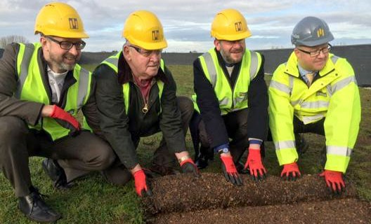 Project managers from Midas group lay out the final piece of turf at Filwood