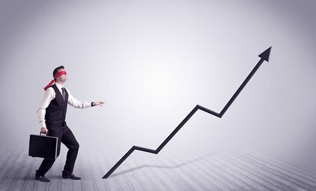 Blindfolded business man navigating upward curve on graph